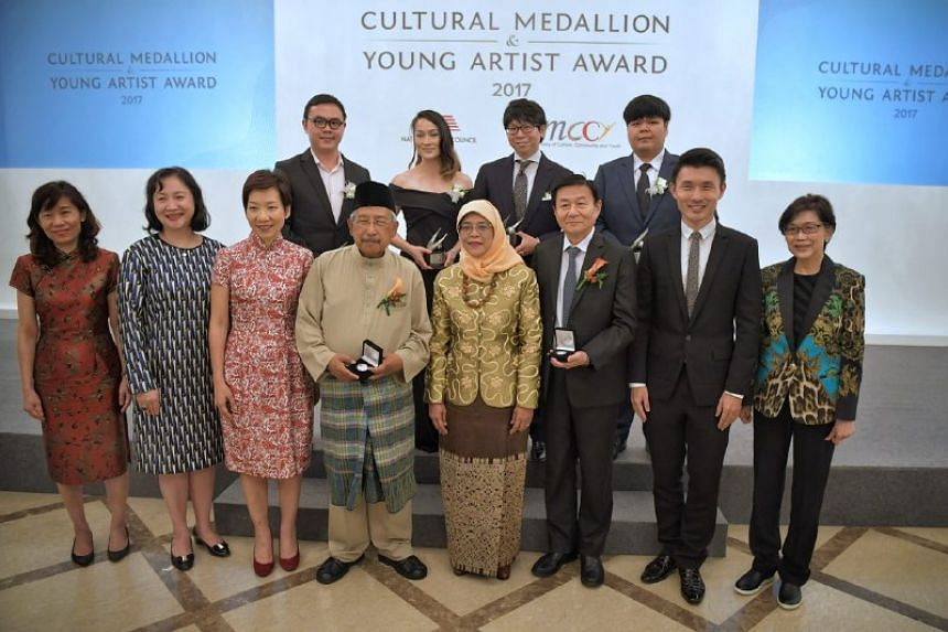 President Halimah Yacob (front row, fifth from left) with Cultural Medallion recipients Djamal Tukimin (front row, fourth from left) and Law Wai Lun (front row, sixth from left). Also pictured are Young Artist Award recipients with Minister for Cultu