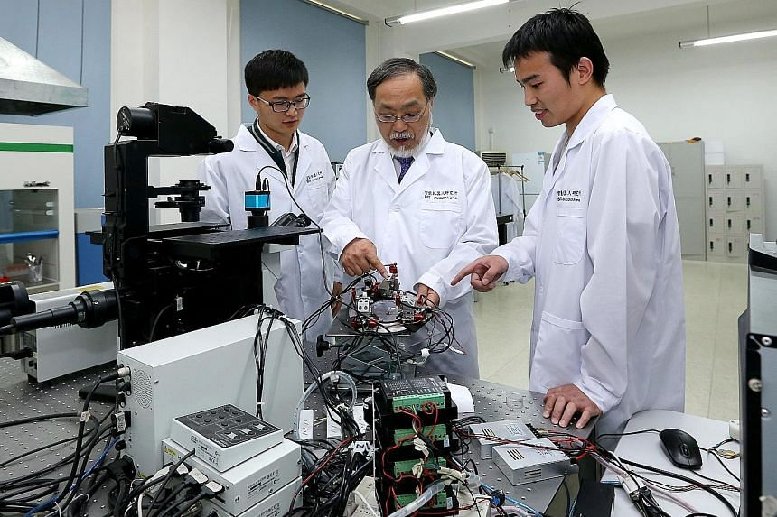 Japanese robotics expert Toshio Fukuda (centre) with two Chinese students at the Beijing Institute of Technology. A Forbes report says more Chinese who studied or worked overseas are returning home. Experts in the science and technology sector have m