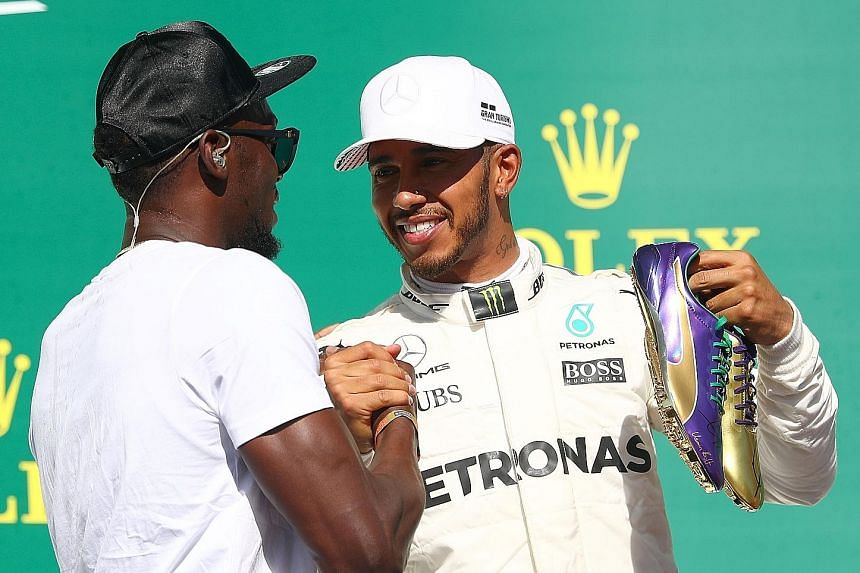 """Top: Retired Jamaican sprint legend Usain Bolt in his signature """"lightning Bolt"""" pose before the start of Sunday's US Grand Prix in Austin, Texas. Above: Bolt presenting race winner Lewis Hamilton with a pair of spikes made for his August World Champ"""