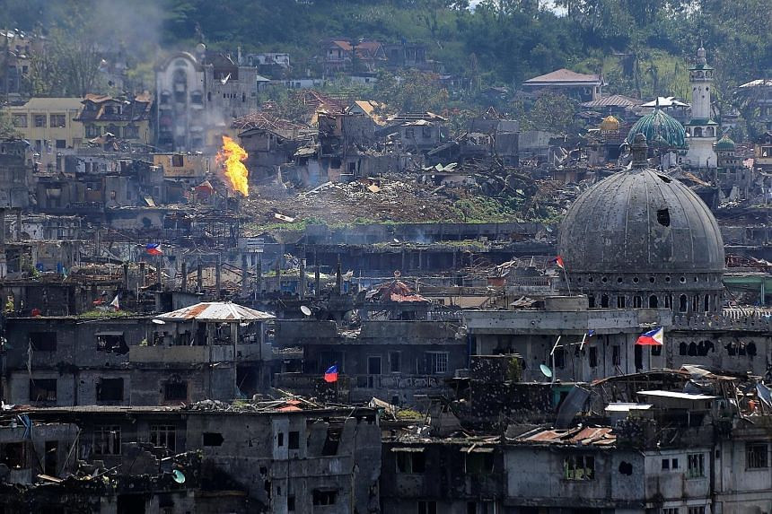 Damaged buildings in war-torn Marawi City after government troops cleared the last area of pro-ISIS militants yesterday. More than 1,000 militants, government troops and civilians have been killed in the conflict which began on May 23.