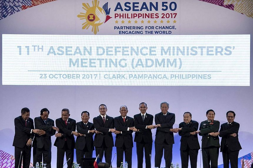 The Association of Asean Defence Ministers link arms during the 11th Asean Defence Ministers' Meeting opening ceremony in Manila on Oct 23, 2017.