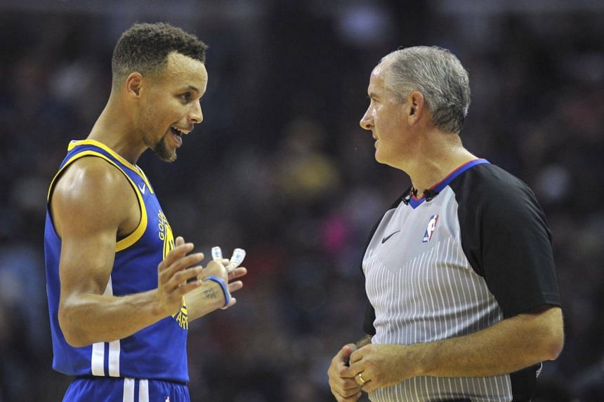 Stephen Curry talks with referee Scott Wall during the first half of the game.