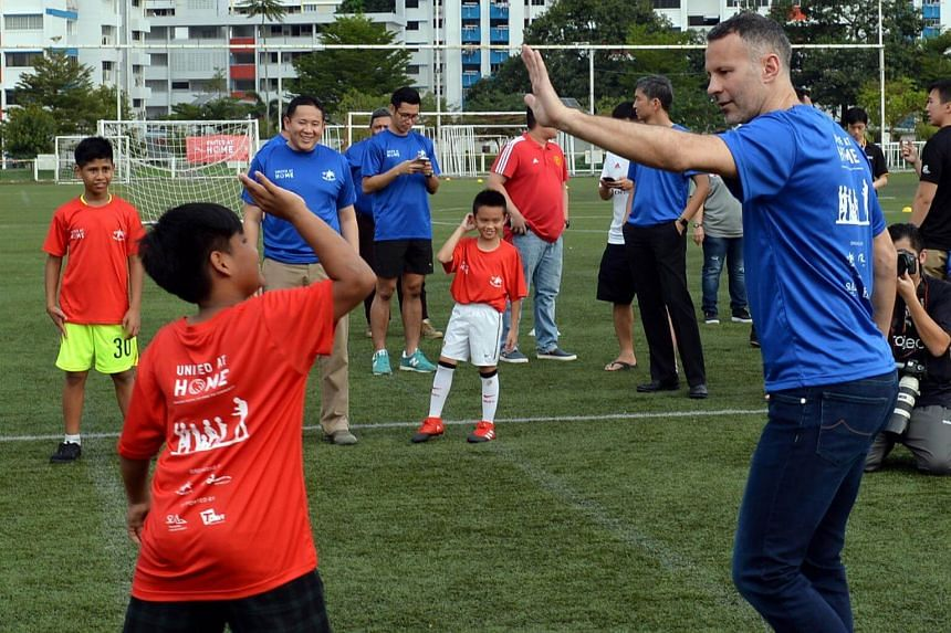 Former Manchester United player Ryan Giggs giving a high five to one of the participants during his visit to Home United Youth Football Academy (HYFA) soccer clinic.