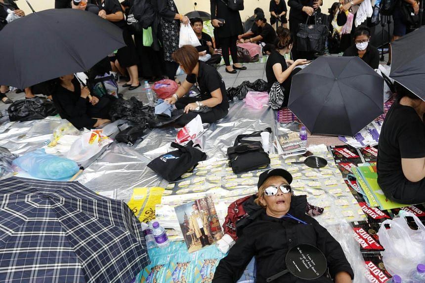 A Thai mourner sleeps next a portrait of the late Thai King Bhumibol Adulyadej, as people line up to wait to take part in the Royal Cremation ceremony of the late King Bhumibol Adulyadej, near of Sanam Luang in Bangkok, Thailand, on Oct 24, 2017.