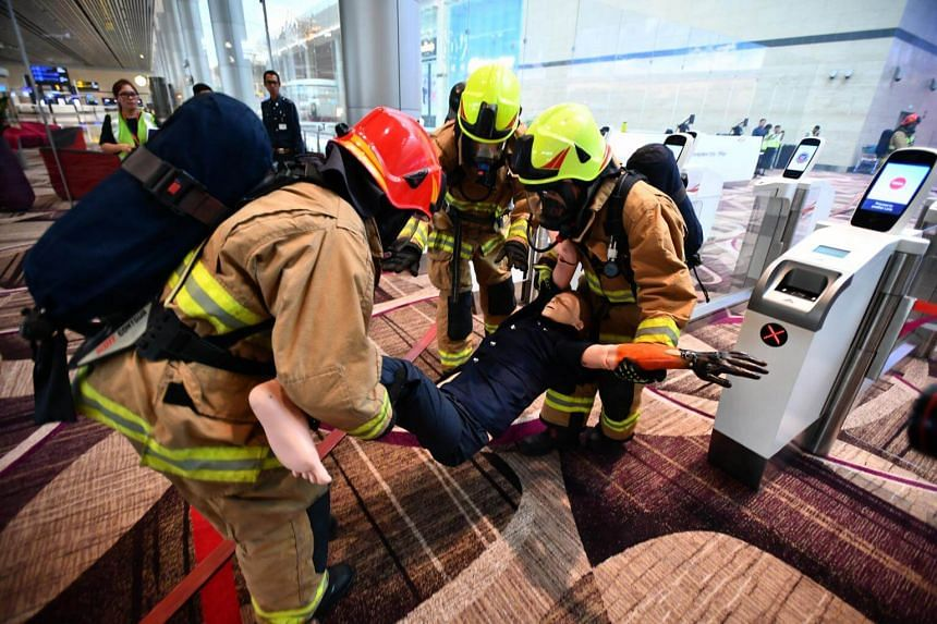Airport emergency service officers rescuing a casualty during a fire evacuation exercise.