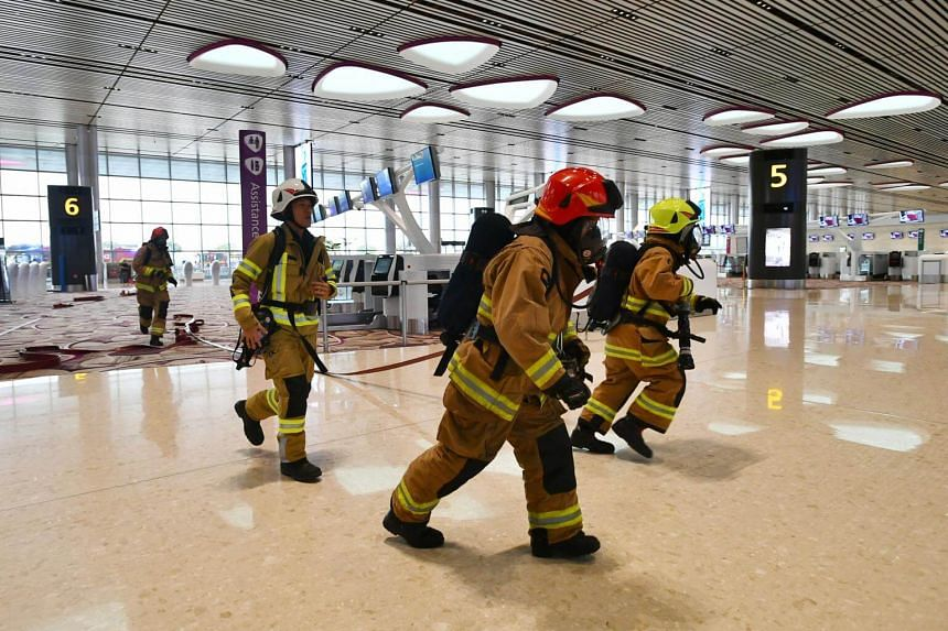 Airport emergency service officers in action during a fire evacuation exercise.