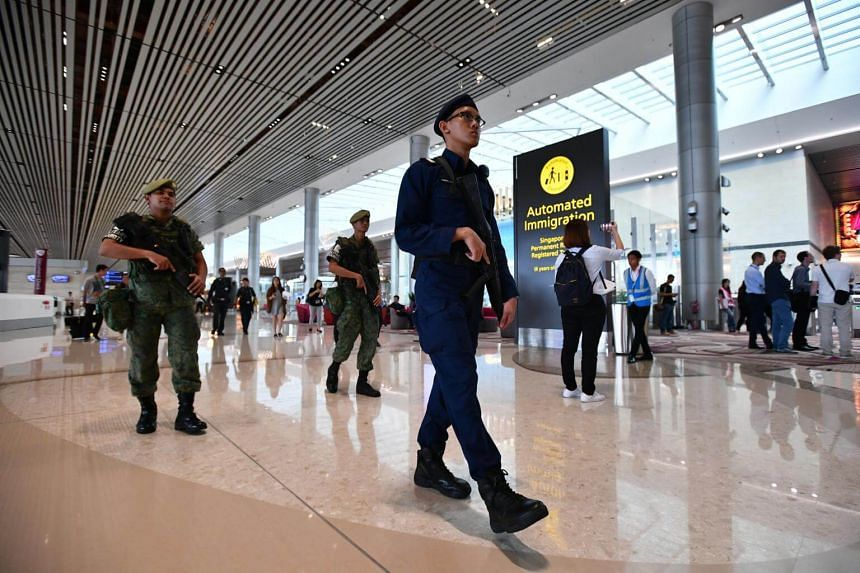 Police officer and Singapore Armed Forces soldiers patrolling the Departure Hall.