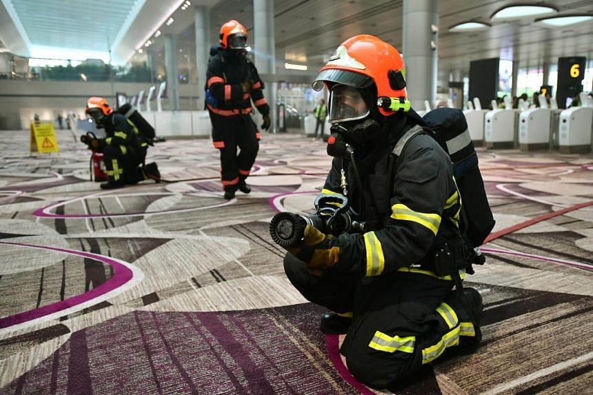 Singapore Civil Defence Force officers in action during a fire evacuation exercise.