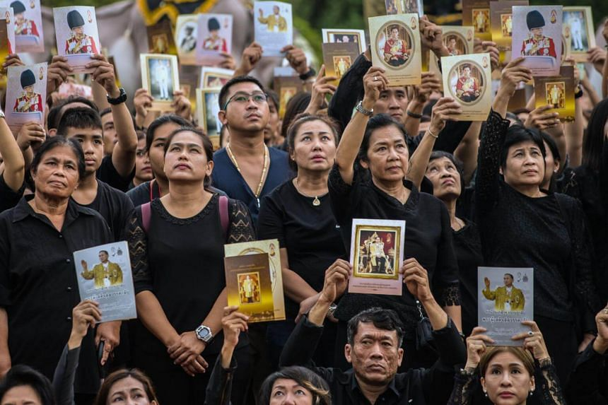 People display images of the late Thai King Bhumibol Adulyadej during a ceremony marking one year since his death, in a field in Ayutthaya on Oct 13, 2017.