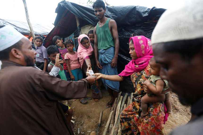 A local resident donates money to the Rohingya refugees at the Palong Khali refugee camp near Cox's Bazar, Bangladesh on Oct 23, 2017.