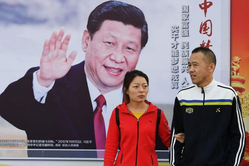 People walk past a poster of Chinese President Xi Jinping beside a sidewalk in Beijing, during the 19th Communist Party Congress on Oct 23, 2017.