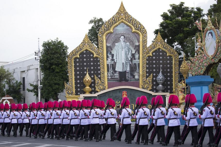 Thai royal guards march next to a portrait of the late Thai King Bhumibol Adulyadej at the Royal Plaza in Bangkok, Thailand, on Oct 23, 2017.