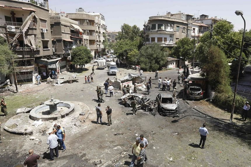Syrians gathering to inspect the damage at the site of a suicide bomb attack in the capital Damascus' eastern Tahrir Square district, on July 2, 2017.