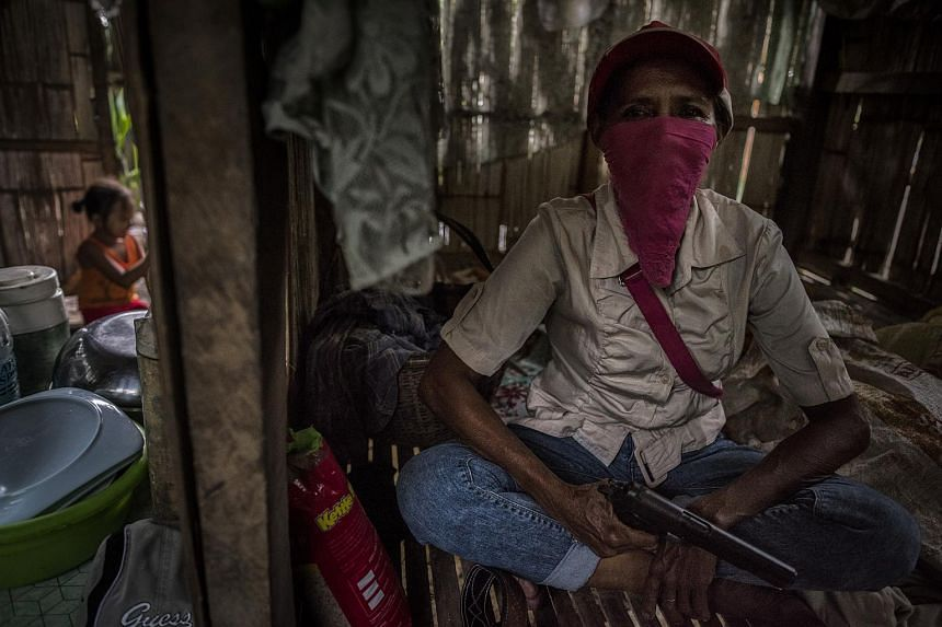 Commander Ilangilang, a member of a Christian militia unit, holds a pistol inside a hut in Kauran, Philippines, on Sept 19, 2017.