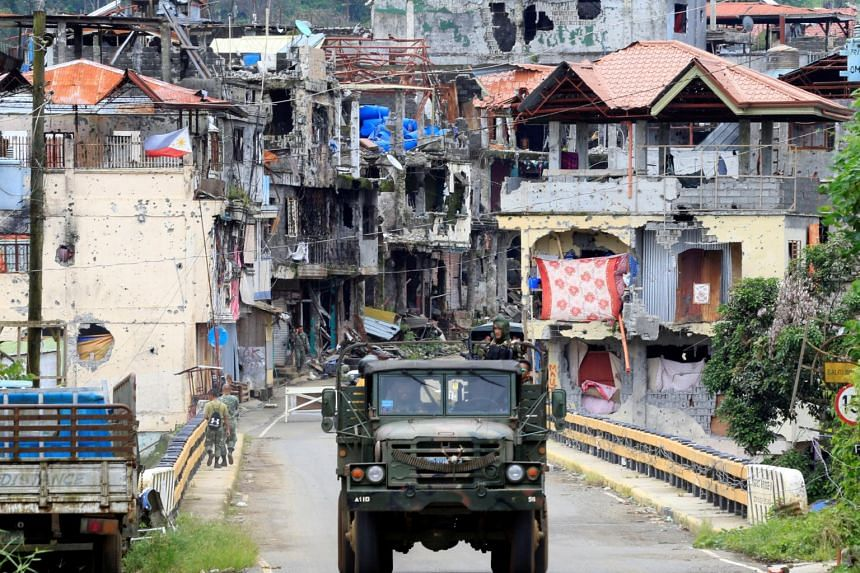Soldiers on a military truck drive past houses and buildings damaged after government troops cleared the area from pro-Islamic State militant groups inside the war-torn Marawi city.