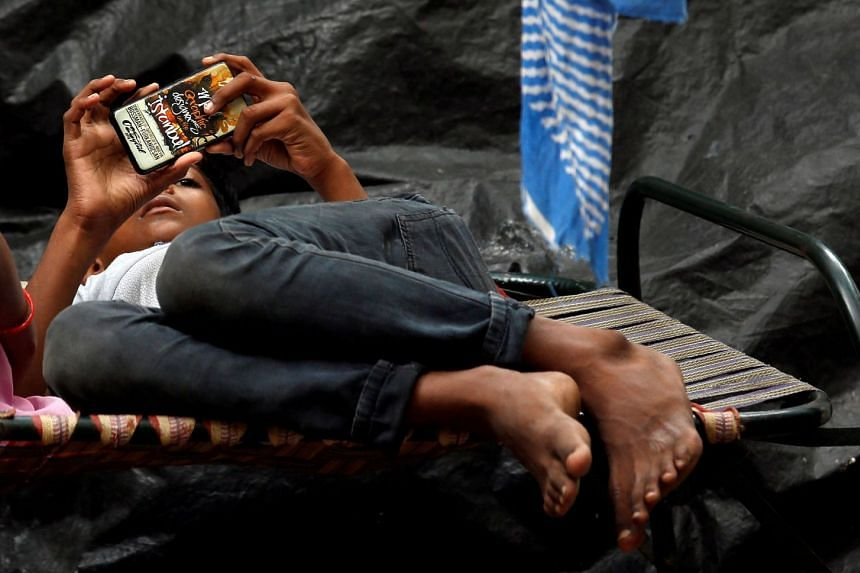A boy watches a movie on his mobile phone in Kolkata, India.