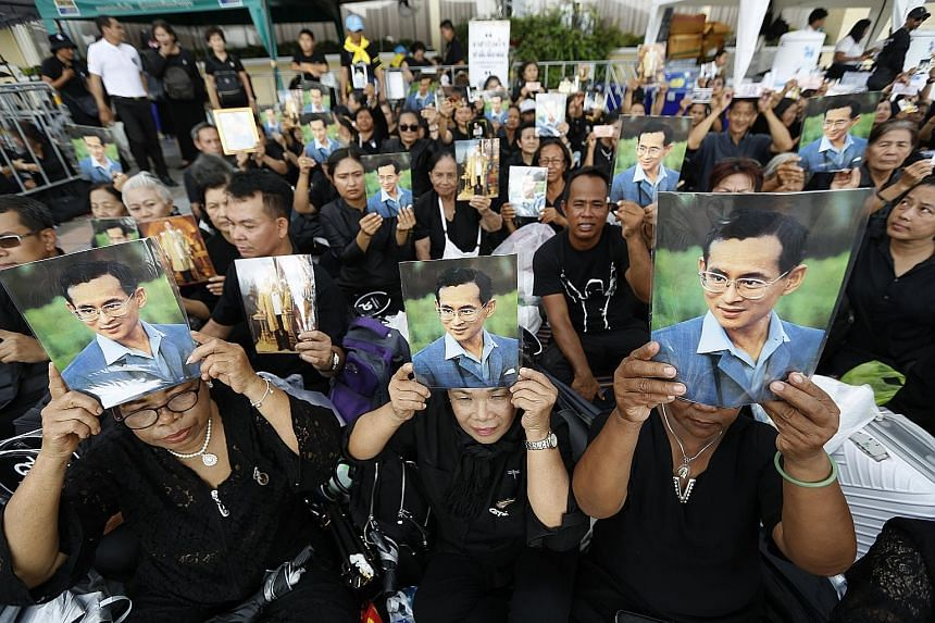 Mourners holding portraits of the late King Bhumibol Adulyadej as they wait to take part in the royal cremation ceremony. King Bhumibol died in October last year at the age of 88.