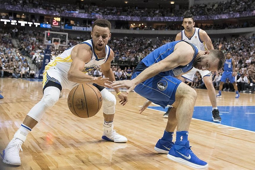 Golden State Warriors guard Stephen Curry stealing the ball from Dallas Mavericks' J.J. Barea. The champions have a 2-2 record this season.