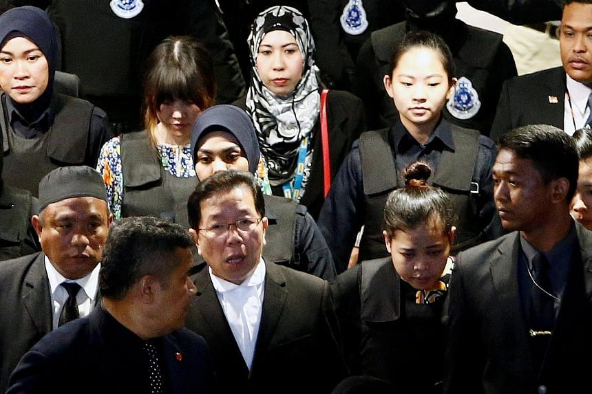 The accused - Indonesian Siti Aisyah (front, second from right) and Vietnamese Doan Thi Huong (back, second from far left) - being escorted as they and the rest of the court visited the Kuala Lumpur International Airport 2 yesterday.