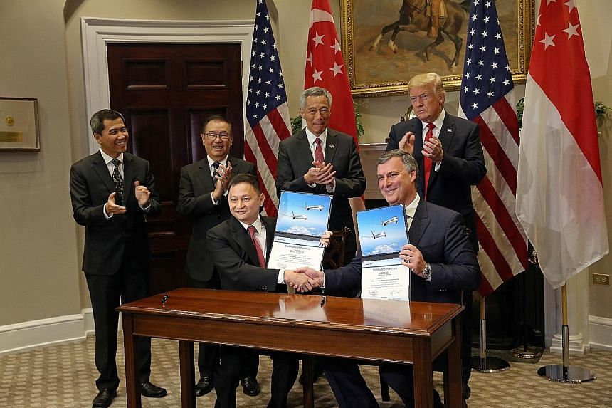 US President Donald Trump, Prime Minister Lee Hsien Loong and (from left) Mr Lau Hwa Peng, SIA senior vice-president, engineering, and SIA chairman Peter Seah witnessed the signing of the agreement between SIA CEO Goh Choon Phong (seated) and Boeing