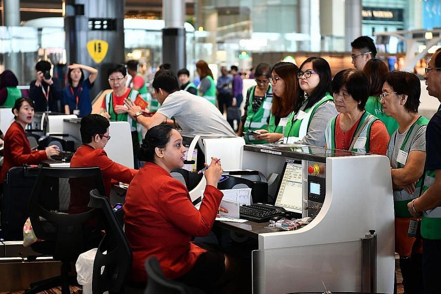 """Staff at the check-in counters going through procedures with mock passengers. T4 also offers a start-to-end automated process from check-in to boarding. Airport emergency service personnel rescuing a """"casualty"""" during the fire evacuation exercise at"""