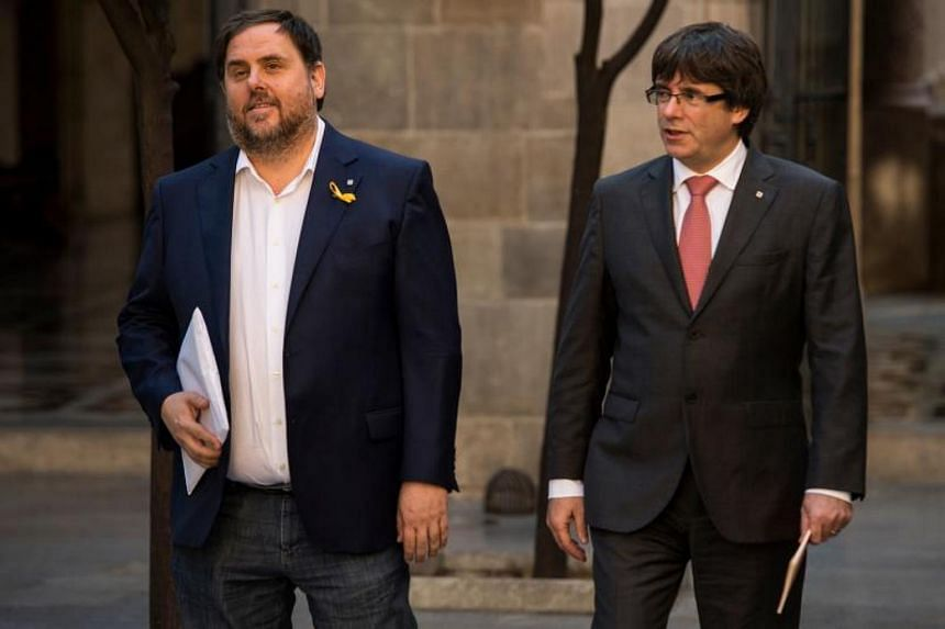 Catalan regional vice-president Oriol Junqueras (left) and Catalan regional government president Carles Puigdemont arrive to attend a regional goverment meeting at the Generalitat Palace in Barcelona on Oct 24, 2017.
