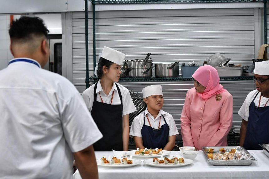 President Halimah Yacob  with students (from left) Murial Chua Ming Hui, Neo Boon Fan and Muhammad Yamin Mohd Yazid, all 16 years old, at the Istana Kitchen on Oct 25, 2017.
