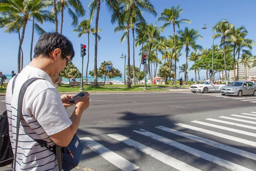 """The law imposes fines on anyone caught crossing a street while """"viewing"""" a cellphone or similar device."""