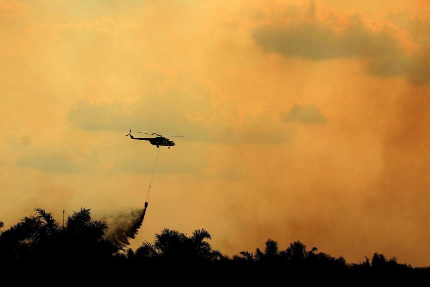 A helicopter conducting waterbomb operations to put out fires in Ogan Ilir, South Sumatra, on Aug 6, 2017. The number of forest fires across Indonesia fell by more than 30 per cent this year.