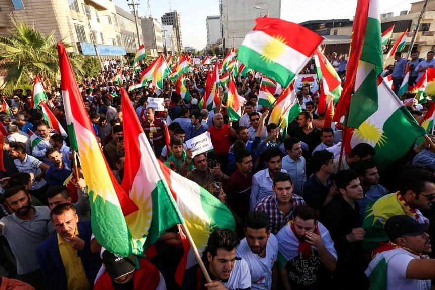 Iraqi Kurds wave flags of Iraqi Kurdistan and shout slogans during a demonstration outside the UN Office in Arbil on Oct 21, 2017.