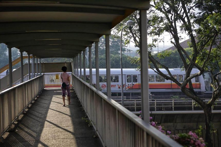 A pedestrian on an overhead bridge looks on as a train inches towards Bishan MRT station from Ang Mo Kio on Oct 25, 2017.