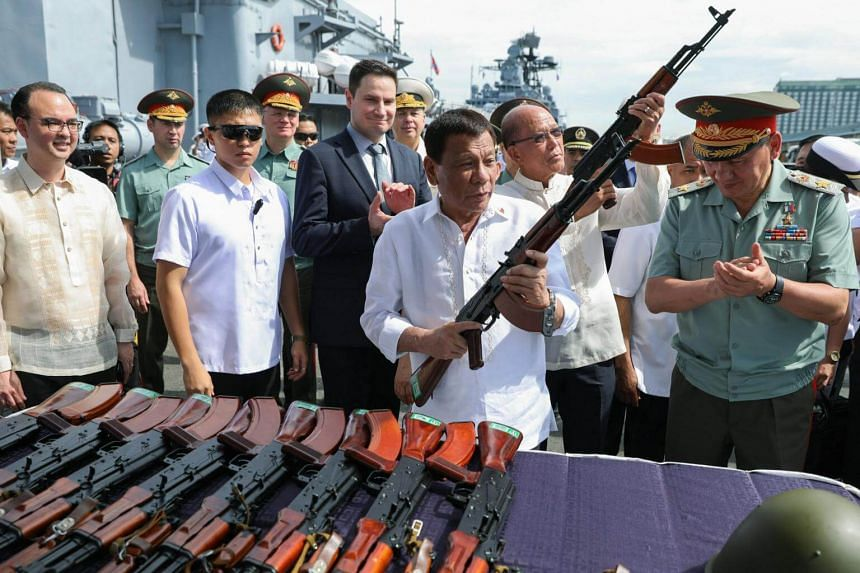 President Rodrigo Duterte (centre) inspects an AK-74M Kalashnikov Rifle donated by the Russian Federation during the ceremonial turnover in Manila on Oct 25, 2017.