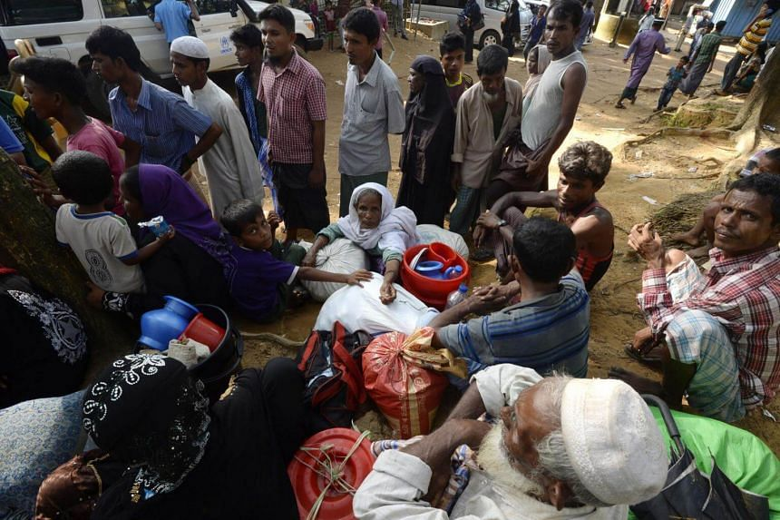 Rohingya refugees rest after crossing into Bangladesh from Myanmar at Kutupalong refugee camp in the Bangladeshi district of Ukhia on Oct 24, 2017.