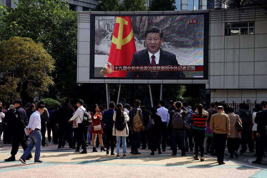A live broadcast of Chinese President Xi Jinping introducing the Politburo Standing Committee is displayed on a TV screen in Shanghai on Oct 25, 2017.