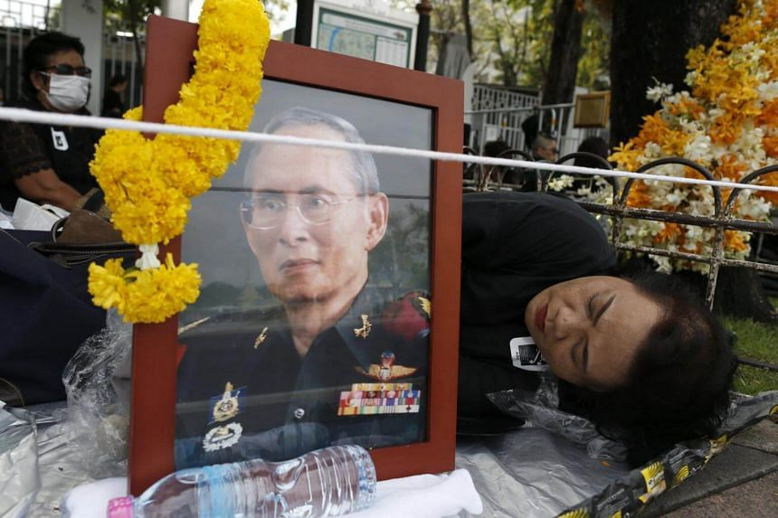 Thai mourner sleeps next to a framed photograph of the late Thai King Bhumibol Adulyadej on Oct 25, 2017.
