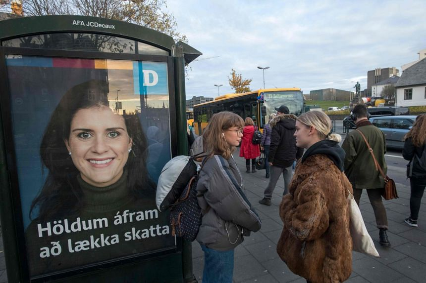 """People wait at a bus stop with an election poster from the Independence party which reads """"Continue to lower taxes"""" in Reykjavik, Iceland."""