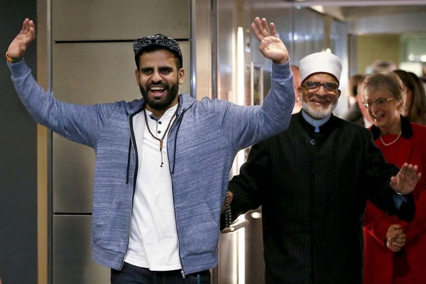 Ibrahim Halawa gestures to wellwishers, family and friend, next to his father Hussein Halawa (R) as he arrives at Dublin Airport.