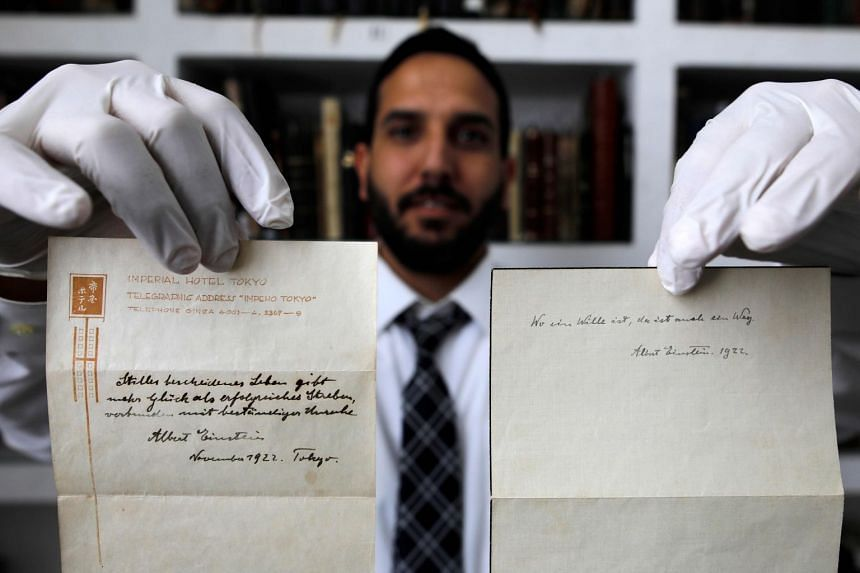 Auctions house owner Gal Winner displays two notes written by Albert Einstein.