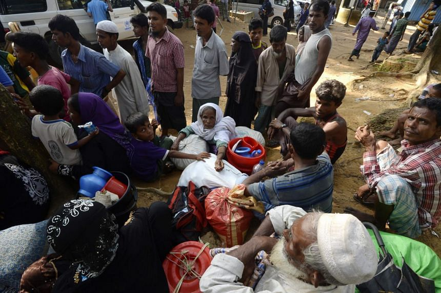 Rohingya refugees rest after crossing into Bangladesh from Myanmar at Kutupalong refugee camp in the Bangladeshi district of Ukhia.