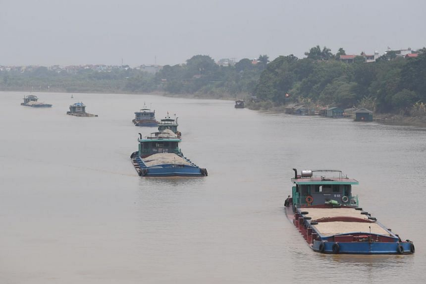 Boats transporting sand sail along the Red River in Hanoi. Vietnam needs about 100 million cubic metres of sand every year for construction projects across the country.