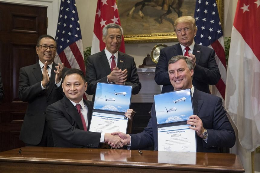 Boeing Executive Vice President Kevin McAllister (right) and CEO of Singapore Airlines Goh Choon Phong (centre, left) along US President Donald Trump (centre, right) and Lee Hsien Loong (centre) of Singapore attend a signing ceremony for airplane sal
