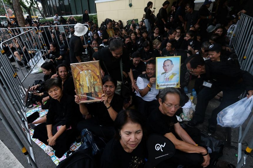 Mourners hold portraits of Thailand's late King Bhumibol Adulyadej as they wait to attend the Royal Cremation ceremony near the Grand Palace in Bangkok, Thailand.