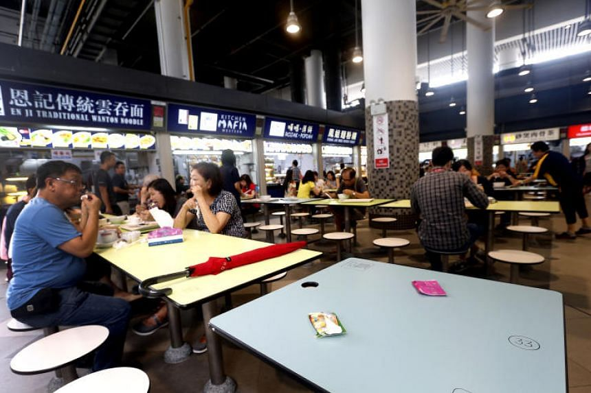 An umbrella and packets of tissue used to chope seats at the food centre in Our Tampines Hub.