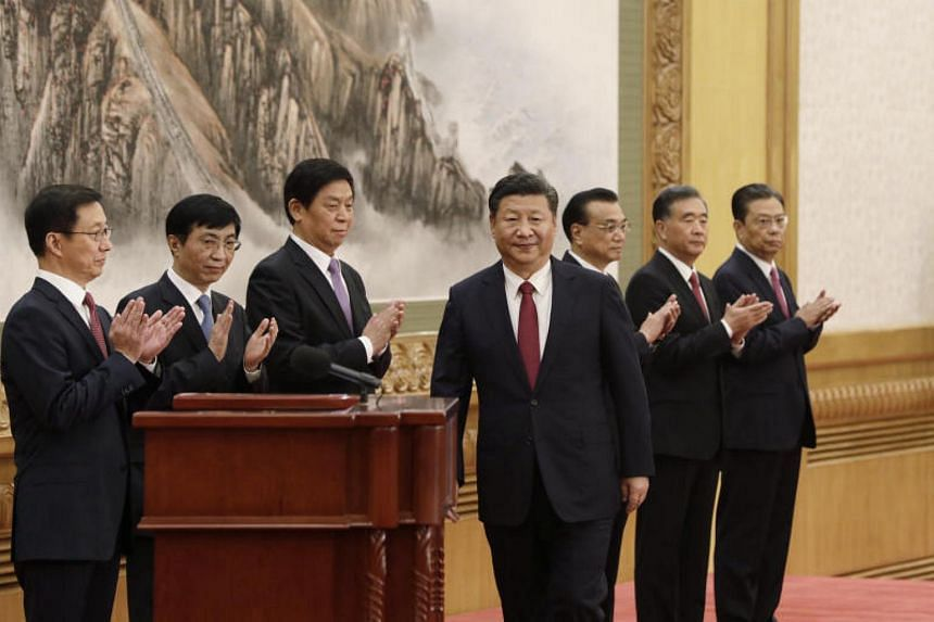 President Xi Jinping approaches the podium to speak as the other six members of China's new Politburo Standing Committee applaud.