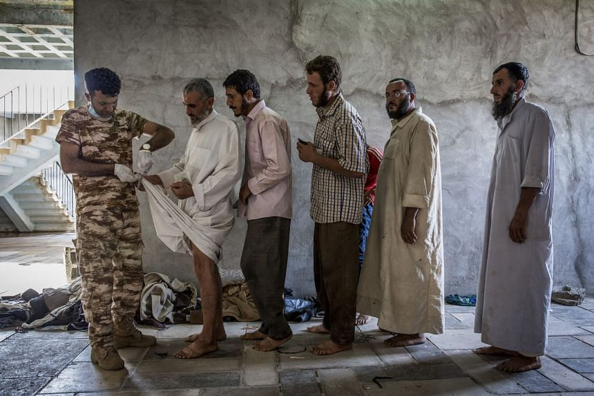 Men suspected of being ISIS fighters are searched at a security screening centre near Kirkuk, Iraq, Oct 1, 2017.