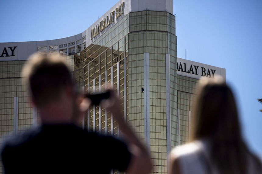 People take photos of broken windows on the 32nd floor of a hotel used by gunman Stephen Paddock to fire on an outdoor concert.