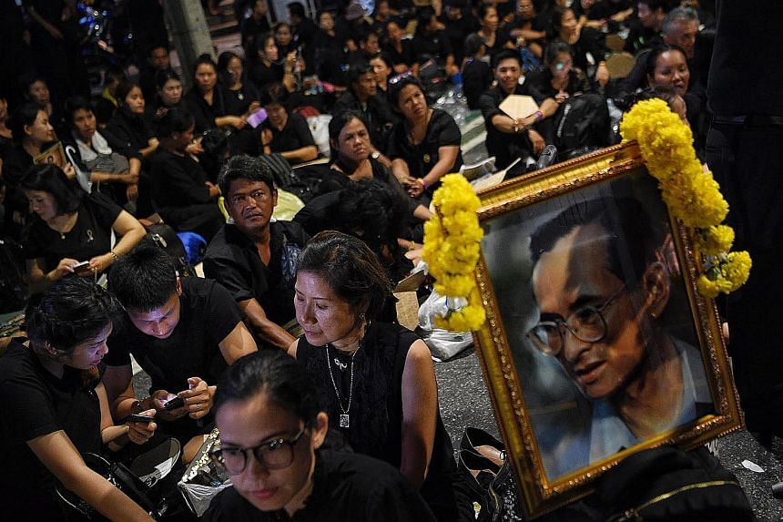 People queueing along Phra Athit Road yesterday to enter the area around Sanam Luang in Bangkok, where the royal funeral procession for the late King Bhumibol Adulyadej will take place. Many have been waiting for days to see this rare ceremony up clo