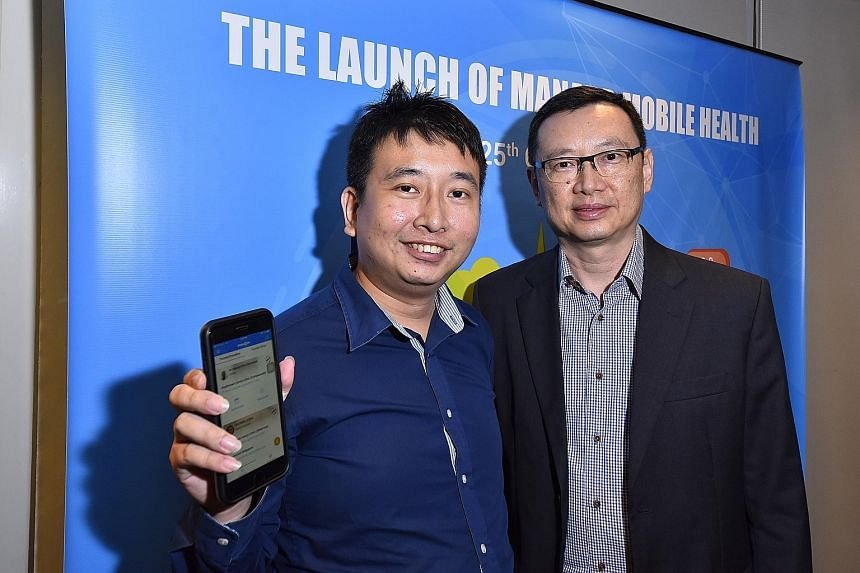 """Mr Kaw Cong Kai (far left), 30, likes the app, saying: """"It's really convenient."""" With him is Dr David Cheong."""