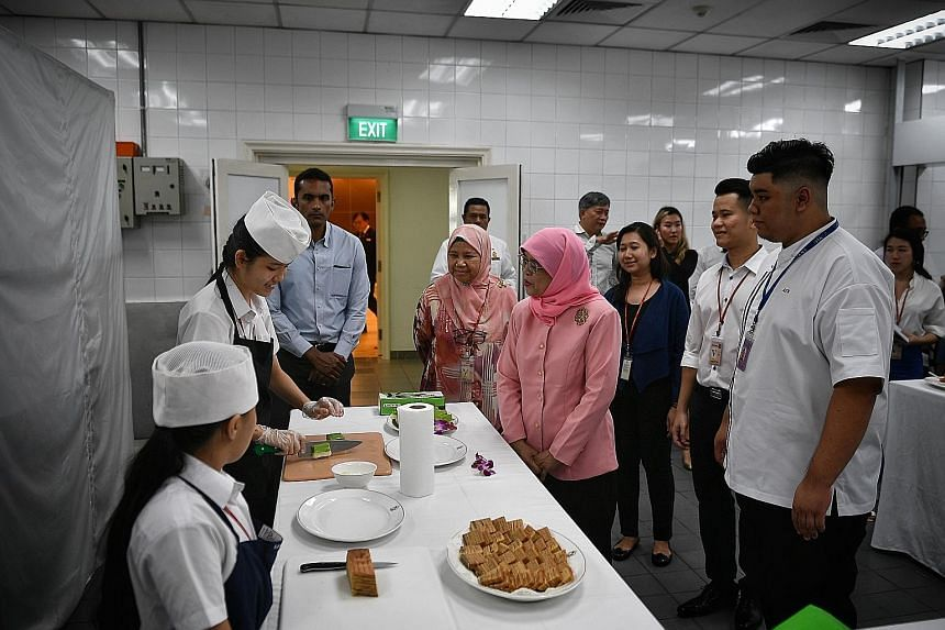 Murial Chua, 16, cutting kueh as she chats with President Halimah Yacob at the Istana kitchen, where the teen has learnt to make cookies and kueh over the past two weeks.