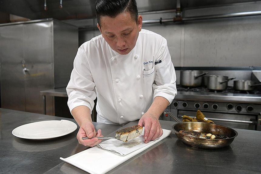 MBS executive chef Dave Heng (above) preparing a dish of sea bass. MBS is targeting that by 2020, half of all seafood items on the menus at its hotel and nine restaurants, including db Bistro (below), will be from sustainable sources.
